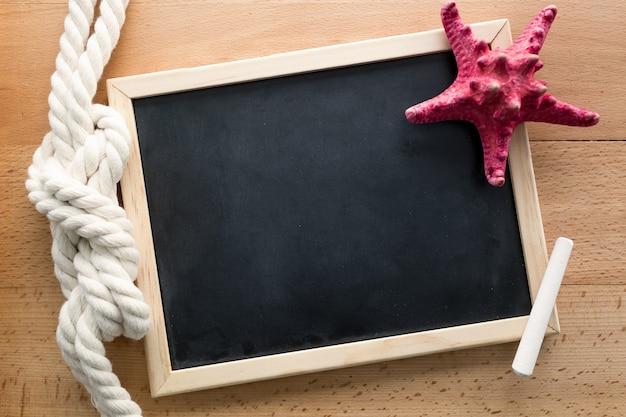 Plan horizontal d'un tableau noir propre décoré par un nœud marin et une étoile de mer