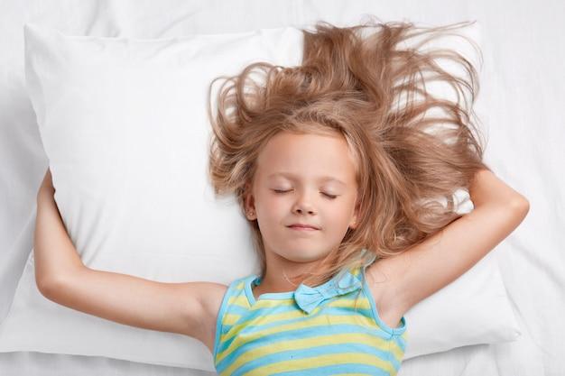 Plan intérieur d'une adorable petite fille aux cheveux clairs non peignés, garde les mains sous un oreiller doux, vêtu d'un pyjama, pose dans un lit confortable seul. enfants, repos nocturne et concept de mode de vie