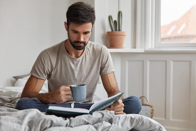 Plan intérieur d'un beau mec barbu posant à la maison tout en travaillant
