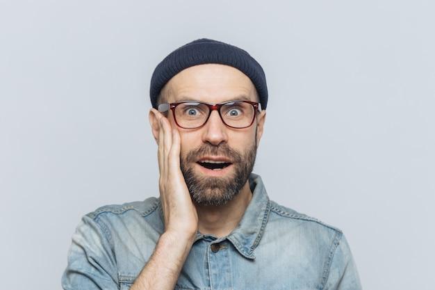 Plan intérieur d'un bel homme surpris, garde la main sur la joue, porte des lunettes et des vêtements élégants