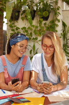Plan intérieur de deux étudiantes accros aux technologies modernes