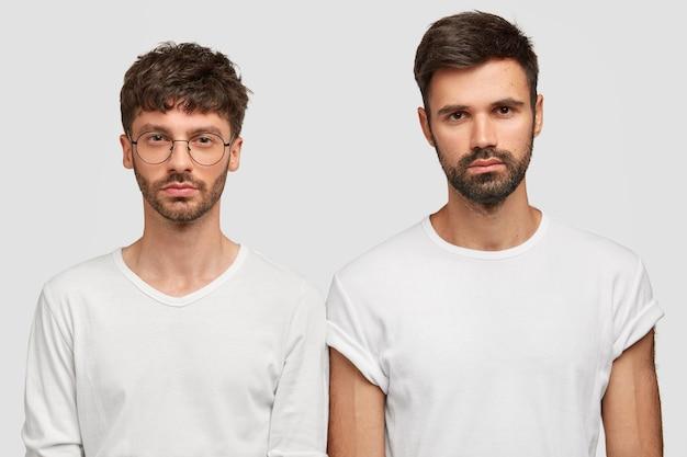 Plan intérieur de deux hommes sérieux qui regardent directement la caméra, portent des vêtements décontractés, ont des chaumes
