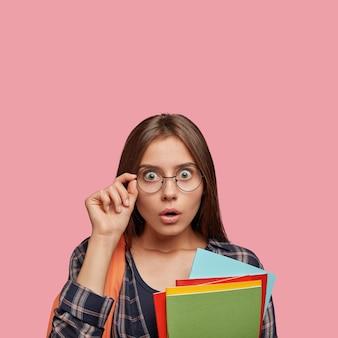 Plan intérieur d'un étudiant stupéfait posant contre le mur rose avec des lunettes