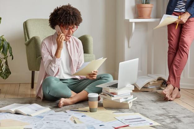 Plan intérieur d'une femme d'affaires indignée crie à un collègue via un téléphone portable