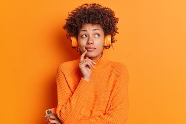 Plan intérieur d'une femme afro-américaine pensive concentrée au-dessus garde le doigt sur le menton considère quelque chose à l'esprit tout en écoutant une mélodie calme dans des écouteurs stéréo