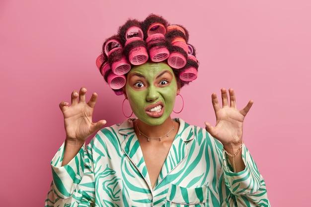 Plan intérieur d'une femme au foyer fait une grimace de colère, lève les mains comme des pattes, serre les dents, porte des bigoudis, un masque de beauté pour le rajeunissement, vêtue de vêtements domestiques. femmes, soins de la peau, cosmétologie.