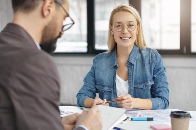Plan intérieur d'une femme blonde ayant une conversation d'affaires avec un collègue