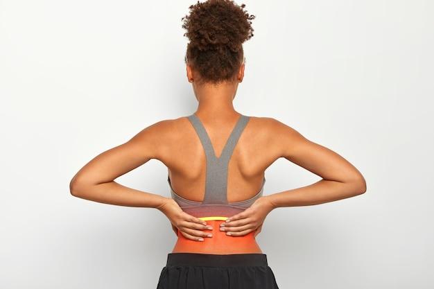 Plan intérieur d'une femme bouclée sans visage touche la zone problématique du dos, souffre de crampes douloureuses, vêtue de vêtements de sport décontractés, isolée sur fond blanc. soins de santé et concept médical