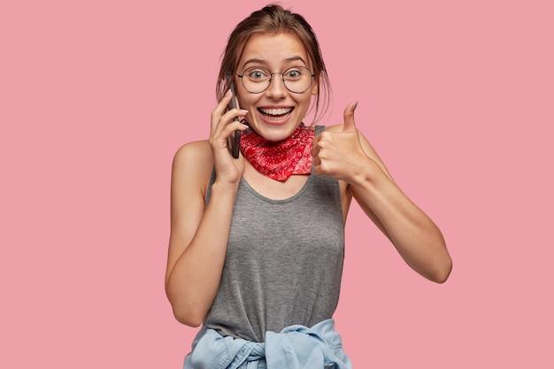 Plan intérieur d'une femme caucasienne joyeuse montre un geste correct, garde le pouce levé, exprime son approbation, parle via un téléphone portable