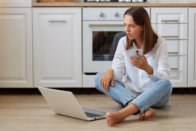 Plan intérieur d'une femme effrayée en chemise blanche et jeans, assise sur le sol avec un téléphone portable dans les mains, regardant un écran d'ordinateur portable avec une expression choquée, voit quelque chose d'étonné.
