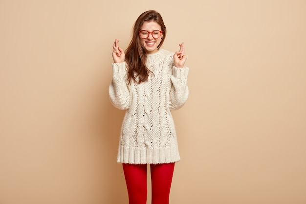 Plan intérieur d'une femme heureuse avec une expression faciale joyeuse, croise les doigts, espère que les rêves deviennent réalité, porte un long pull et des collants, isolée contre un mur beige croyez seulement en mieux!
