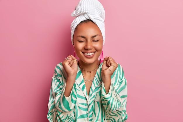 Plan intérieur d'une femme heureuse à la peau foncée, les yeux fermés, serre les poings, se réjouit de la bonne nouvelle, vêtue d'une robe domestique, d'une serviette de bain enveloppée. la femme au foyer passe le week-end à la maison. atmosphère chaleureuse