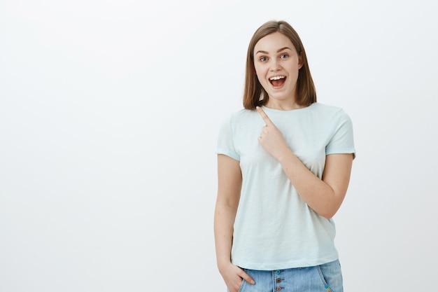 Plan intérieur d'une femme mignonne émerveillée, énergique et optimiste, en t-shirt à la mode souriant joyeusement pointant vers le coin supérieur gauche avec l'index près de la poitrine, profitant de passer du temps amusant et amusé