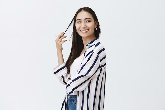 Plan intérieur d'une femme à la mode séduisante féminine en chemisier rayé, tournant à droite tout en jouant avec une mèche de cheveux et souriant joyeusement, étant satisfait du projet de conception fini sur un mur gris