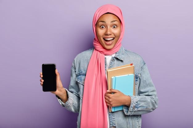 Plan intérieur d'une femme musulmane optimiste à la peau sombre présente un gadget cool