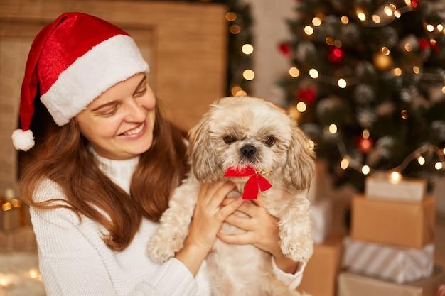 Plan intérieur d'une femme souriante et satisfaite posant près d'un arbre de noël avec de nombreuses boîtes de cadeaux, jouant avec son chien pékinois, exprimant des émotions positives, portant un pull blanc et un bonnet de noel.