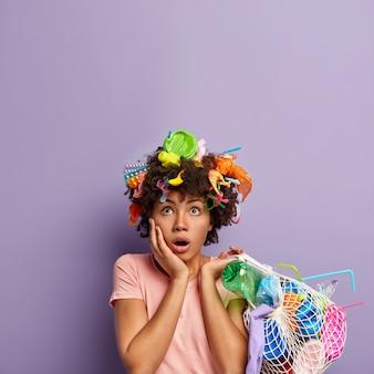 Plan intérieur d'une femme surprise à la peau foncée regarde avec embarras au-dessus, touche la joue, a des déchets dans les cheveux tient un sac en filet plein de litière porte un t-shirt décontracté est déçu. écologie, pollution