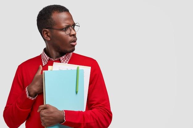 Plan intérieur d'un homme noir indigné concentré sur le côté avec une expression terrible, un regard effrayé, porte des lunettes rondes, tient des dossiers et des papiers avec un stylo