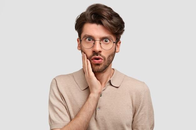 Plan intérieur d'un homme sérieux barbu avec une expression effrayée, touche la joue, a du chaume sombre, vêtu d'une tenue décontractée, se dresse contre un mur blanc