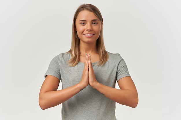 Plan intérieur d'une jeune femme adulte gardant les paumes jointes en position de prière. méditant, souriant et garde les yeux ouverts, isolé sur fond blanc