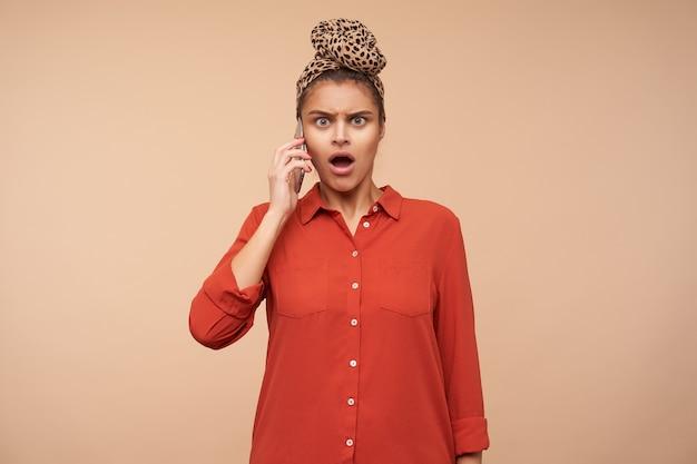 Plan intérieur d'une jeune femme brune choquée avec un maquillage naturel fronçant les sourcils tout en ayant une conversation téléphonique tendue et regardant avec étonnement à l'avant, isolé sur un mur beige