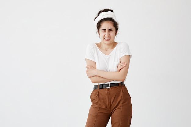 Plan intérieur d'une jeune femme brune dégoûtée dans des vêtements décontractés, debout dans une position fermée, les bras croisés, fronçant les sourcils après avoir vu quelque chose d'horrible.