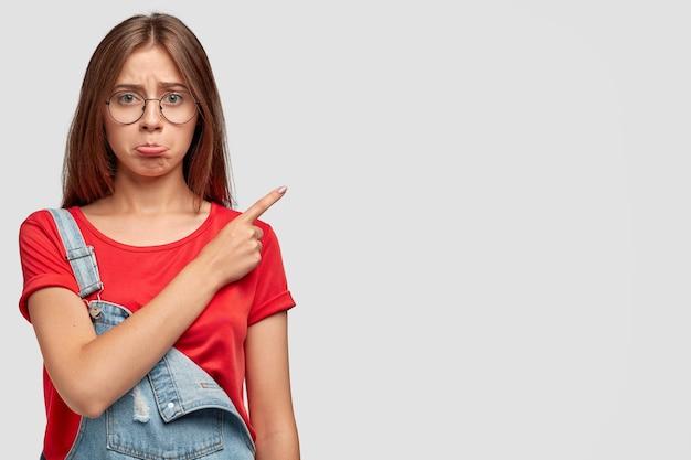 Plan intérieur d'une jeune femme charmante mécontente a une expression offensée, pointe vers le coin supérieur droit, n'aime pas quelque chose, porte un t-shirt rouge décontracté et une salopette en denim, isolée sur un mur blanc