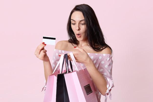 Plan intérieur d'une jeune femme européenne aux cheveux noirs surpris, étonné, tient des sacs, se demande combien d'argent elle a dépensé en achats, porte une carte de crédit, pose sur un mur rose