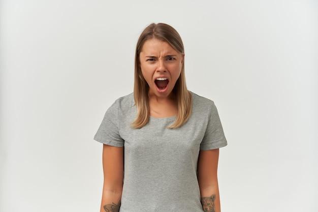 Plan intérieur d'une jeune femme folle et en colère, mettant en vedette la caméra tout en criant sur blanc