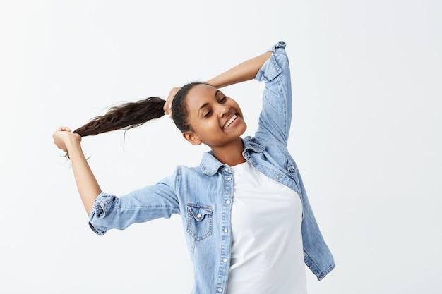 Plan intérieur d'une jeune fille afro-américaine aux longs cheveux ondulés rassemblés en queue de cheval et à la peau foncée vêtue d'une chemise en jean posant à l'intérieur, jouant avec ses cheveux.