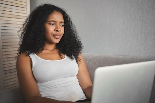 Plan intérieur d'une jeune fille mulâtre à la peau sombre et malheureuse dans des vêtements décontractés, fronçant les sourcils, se sentant frustrée en raison d'une erreur de connexion, utilisant le wi-fi sur un ordinateur portable, étudiant en ligne ou travaillant à distance
