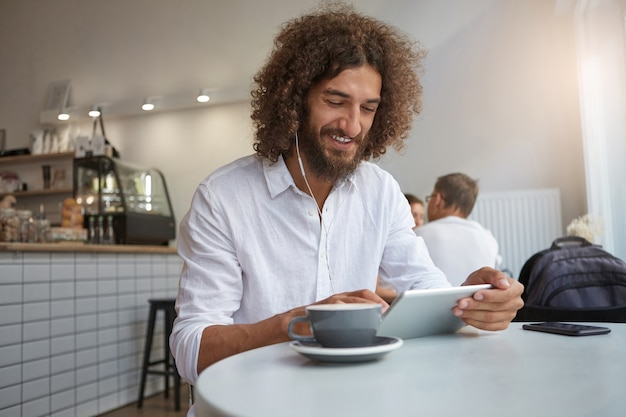Plan intérieur d'un jeune homme gai avec une barbe et des cheveux bruns bouclés posant sur l'intérieur du café, écoutant de la musique et discutant avec des amis tout en prenant une tasse de café