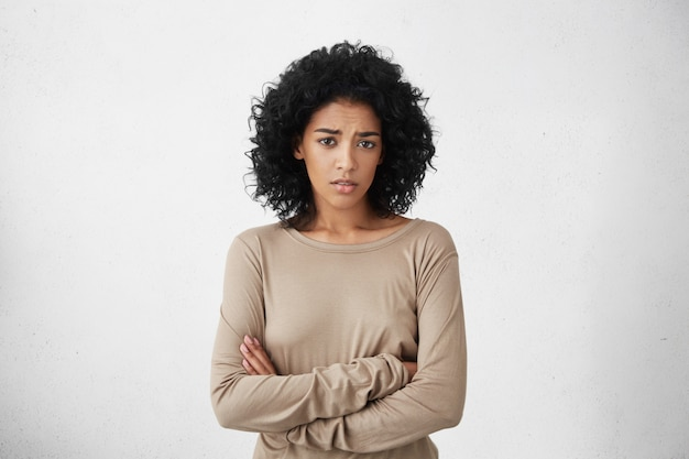 Plan intérieur d'une jeune métisse sceptique se sentant méfiante, son regard exprimant la désapprobation ou le doute, gardant les bras croisés tout en soupçonnant que son mari l'a trompée. horizontal