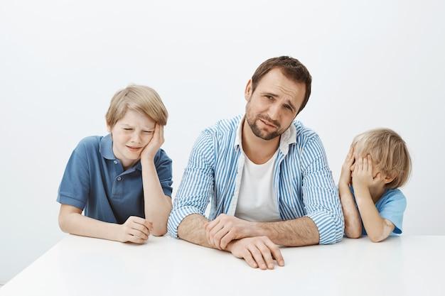 Plan intérieur de jeunes fils mécontents et d'un père assis à table, pleurnichant et bouleversé, fronçant les sourcils de dégoût, voulant manger de la viande pendant que maman donne des légumes