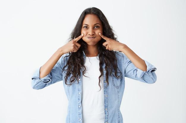 Plan intérieur d'une jolie femme afro-américaine faisant une grimace en soufflant ses joues ayant une expression heureuse. belle jeune femme à la peau foncée vêtue de vêtements décontractés se moquant.