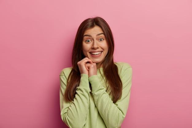 Plan intérieur d'une jolie femme européenne aux cheveux noirs garde les mains près du visage, sourit doucement, a des dents blanches parfaites, une peau saine, porte un pull vert, pose contre un mur rose pastel. joie