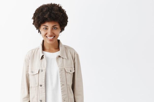 Plan intérieur d'une jolie fille à la peau foncée et à la coiffure afro dans une veste beige à la mode sur un t-shirt, souriant largement et regardant avec une expression assurée et insouciante, se sentant heureux et détendu