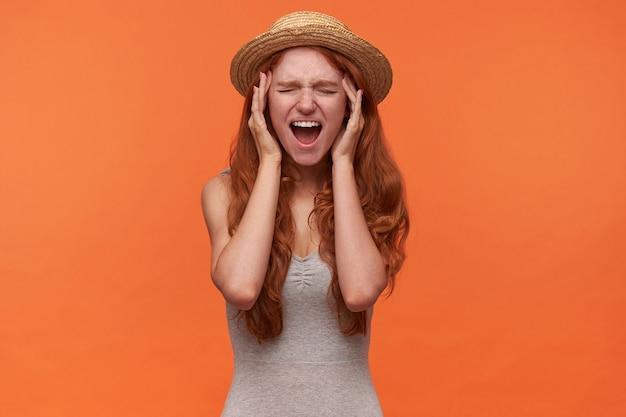 Plan intérieur d'une jolie jeune femme stressée avec des cheveux foxy ondulés posant sur fond orange, tenant les mains sur ses tempes et ouvrant largement la bouche, souffrant de sons forts les yeux fermés
