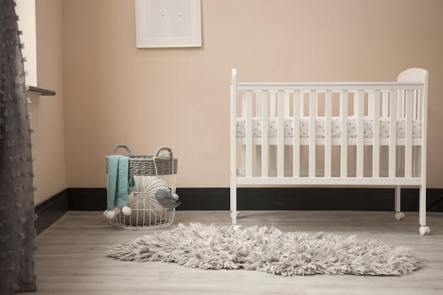 Plan de l'intérieur minimaliste et ensoleillé de la chambre de bébé avec lit d'enfant.