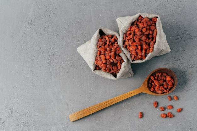 Plan isolé de baies de goji rouges sèches dans deux petits sacs et sur une cuillère à soupe en bois.
