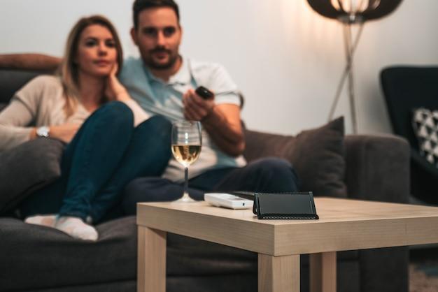 Plan d'un jeune couple devant la télévision à la maison.