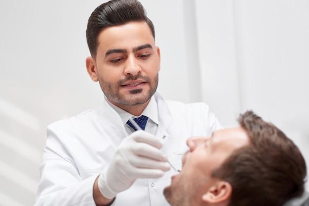 Plan d'un jeune dentiste barbu examinant les dents de son patient travaillant à son bureau examen médical clinique examen traitement personnes concept de dentisterie orale.