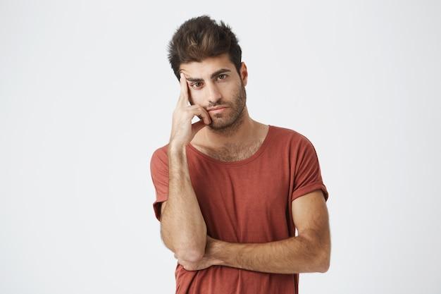 Plan d'un jeune étudiant bronzé sérieux et agacé tenant son doigt sur sa tempe et regardant avec une expression concentrée, comme s'il était fatigué d'écouter quelque chose qu'il avait entendu auparavant