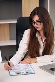 Plan d'une jeune femme d'affaires faisant de la paperasse alors qu'elle était assise à un bureau au bureau.
