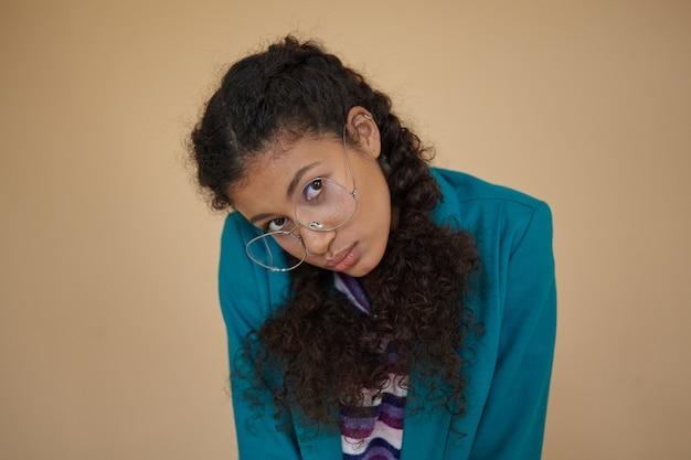 Plan d'une jeune femme brune bouclée à la peau sombre avec des tresses regardant avec un visage calme et gardant les lèvres pliées, vêtue d'un blazer turquoise et d'un pull rayé tout en posant