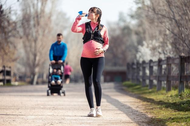 Plan d'une jeune femme enceinte buvant de l'eau dans le parc. au fond, son mari promène son fils avec la charrette.