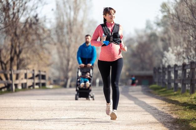 Plan d'une jeune femme enceinte qui court dans le parc. au fond, son mari promène son fils avec la charrette.