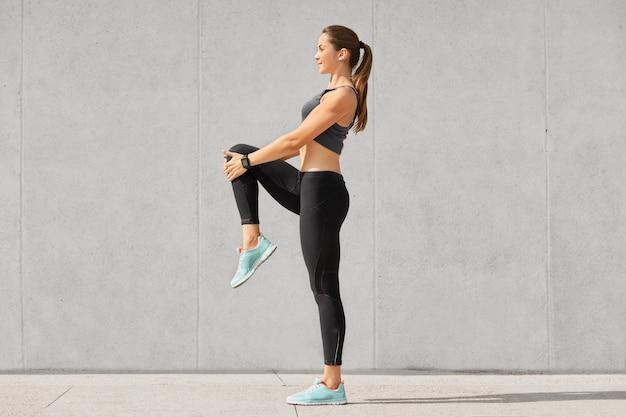 Plan d'une jeune femme flexible se réchauffe avant de faire du jogging sur le stade