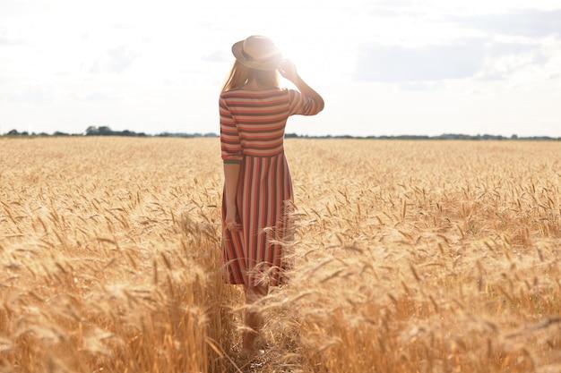 Plan d'une jeune femme en robe rayée posant à l'envers devant la caméra
