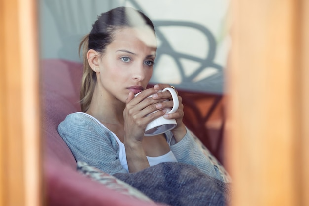 Plan d'une jeune femme sérieuse regardant par la fenêtre en buvant du café sur le canapé à la maison.